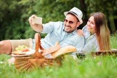 Lyckliga unga par som tar en selfie, medan tycka om picknicktid, parkerar in royaltyfri fotografi