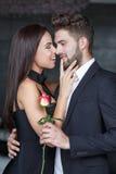 Lyckliga unga skämtsamma par med den röda rosen Royaltyfri Fotografi