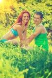 Lyckliga unga sportar kopplar ihop sammanträde på gräs och att se kameran Royaltyfri Foto