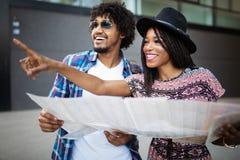 Lyckliga unga svarta par av handelsresande som rymmer översikten i händer arkivfoto