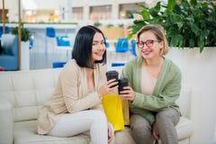 Lyckliga unga trendiga kvinnor som tar ett kaffeavbrott, når att ha shoppat och att le med engå i deras händer mot arkivfoto