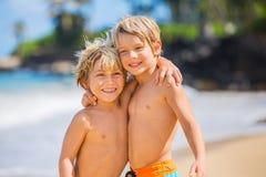 Lyckliga unga ungar som spelar på stranden på sommarsemester Fotografering för Bildbyråer