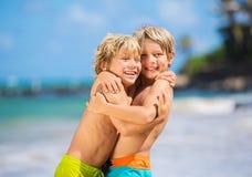 Lyckliga unga ungar som spelar på stranden på sommarsemester Royaltyfri Fotografi