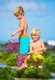 Lyckliga unga ungar som spelar på stranden på sommarsemester Royaltyfria Foton