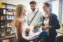 Lyckliga unga universitetsstudenter som tillsammans studerar Grupp av blandras- vänner i högskola arkivbilder