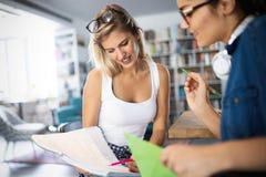 Lyckliga unga universitetsstudenter som tillsammans studerar Grupp av blandras- vänner i högskola royaltyfria bilder