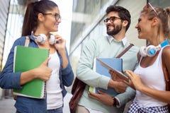 Lyckliga unga universitetsstudenter som tillsammans studerar Grupp av blandras- v?nner i h?gskola arkivbilder