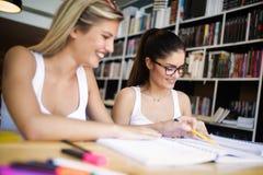 Lyckliga unga universitetsstudentv?nner som studerar med b?cker p? universitetet royaltyfria bilder