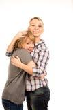 Lyckliga unga vänner som ger varje annan en kram Fotografering för Bildbyråer