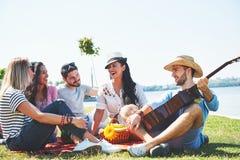 Lyckliga unga vänner som har picknicken i parkera De är alla lyckliga och att ha gyckel, le och spela gitarren Fotografering för Bildbyråer