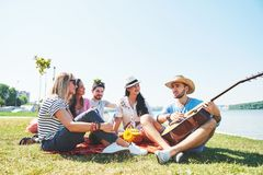 Lyckliga unga vänner som har picknicken i parkera De är alla lyckliga och att ha gyckel, le och spela gitarren Royaltyfria Bilder