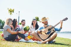 Lyckliga unga vänner som har picknicken i parkera De är alla lyckliga och att ha gyckel, le och spela gitarren Royaltyfri Bild