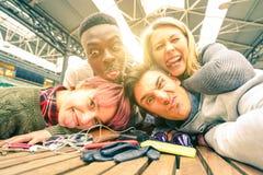Lyckliga unga vänner som inomhus tar selfie med tillbaka belysning royaltyfri foto