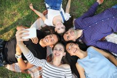 Lyckliga unga vänner som ligger på gräs och tar selfie arkivfoton