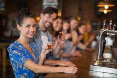 Lyckliga unga vänner som rymmer korta exponeringsglas på räknaren arkivfoto
