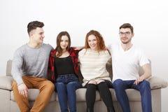 Lyckliga unga vänner, tillfälligt folk som sitter på soffan Royaltyfria Bilder