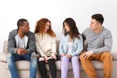 Lyckliga unga vänner, tillfälligt folk som sitter på soffan Arkivfoto