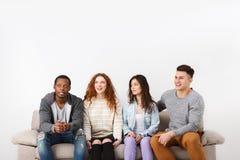 Lyckliga unga vänner, tillfälligt folk som sitter på soffan Royaltyfri Fotografi