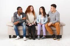 Lyckliga unga vänner, tillfälligt folk som sitter på soffan Royaltyfri Foto