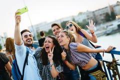 Lyckliga unga v?nner som tar selfie p? gatan royaltyfria foton