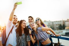 Lyckliga unga v?nner som tar selfie p? gatan arkivbild