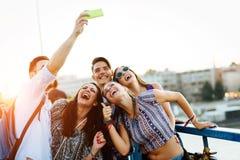 Lyckliga unga v?nner som tar selfie p? gatan royaltyfri fotografi