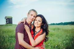 Lyckliga unga vuxna par som är förälskade på fältet Royaltyfria Bilder