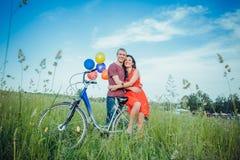 Lyckliga unga vuxna par som är förälskade på fältet Två, man och kvinna som ler och vilar efter cykelridning Arkivbild