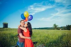 Lyckliga unga vuxna par som är förälskade på fältet Två, man och kvinna som ler och vilar på det gröna gräset Royaltyfri Bild
