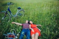 Lyckliga unga vuxna par som är förälskade på fältet Två, man och kvinna som ler och vilar på det gröna gräset Royaltyfria Bilder