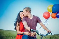 Lyckliga unga vuxna par som är förälskade på fältet Två, man och kvinna som ler och vilar på det gröna gräset Royaltyfri Foto