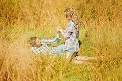 Lyckliga unga vuxna par som är förälskade på fältet Två, man och wom Arkivfoto
