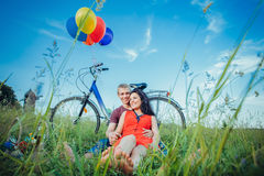 Lyckliga unga vuxna par som är förälskade på fältet Två, mannen och kvinnan har picknicken som ler och vilar på det gröna gräset Arkivfoto