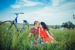 Lyckliga unga vuxna par som är förälskade på fältet Två, mannen och kvinnan har picknicken som ler och vilar på det gröna gräset Royaltyfri Fotografi