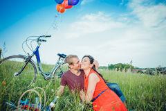 Lyckliga unga vuxna par som är förälskade på fältet Två, mannen och kvinnan har picknicken som ler och vilar på det gröna gräset Royaltyfria Foton