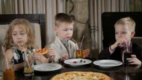 Lyckliga ungar äter pizza i restaurangen stock video