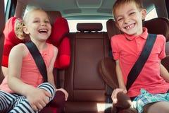 Lyckliga ungar, förtjusande flicka med hennes broder som tillsammans sitter i M royaltyfri foto