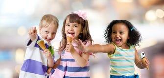 Lyckliga ungar grupperar att äta glass på ett parti royaltyfri bild
