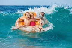 Lyckliga ungar har gyckel i havsbränning på stranden arkivbilder
