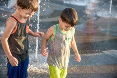 Lyckliga ungar har gyckel som spelar i stadsvattenspringbrunn på varm sommar Royaltyfri Fotografi