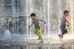 Lyckliga ungar har gyckel som spelar i stadsvattenspringbrunn på varm sommar Royaltyfri Bild