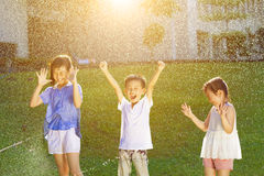 Lyckliga ungar har gyckel som spelar i vattenspringbrunnar Arkivbild