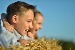 Lyckliga ungar i fält på sommar Arkivfoton