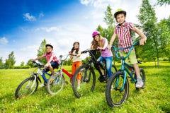 Lyckliga ungar i färgrika cykelhjälmar som rymmer cyklar arkivbild
