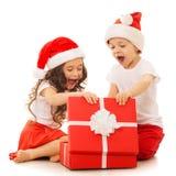Lyckliga ungar i jultomtenhatten som öppnar en gåvaask Arkivfoton