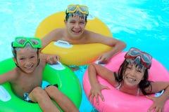 Lyckliga ungar i simbassäng arkivbild