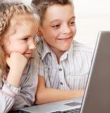 Lyckliga ungar med bärbara datorn Fotografering för Bildbyråer