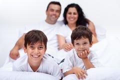 Lyckliga ungar med deras föräldrar som lägger i säng Royaltyfri Bild