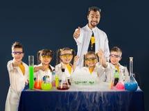 Lyckliga ungar med forskaren som gör vetenskap, experimenterar i laboratoriumet Royaltyfri Bild