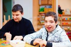 Lyckliga ungar med handikapp framkallar deras fina motoriska expertis på rehabiliteringmitten för ungar med speciala behov Royaltyfria Bilder